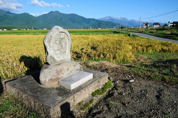 爺ヶ岳と鹿島槍ヶ岳を背景に安曇野の水田地帯に佇む道祖神