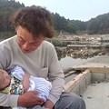 写真: 震災直後のあの日、牡鹿の駐車場に大きく書かれた『HELP出産!日赤病院...
