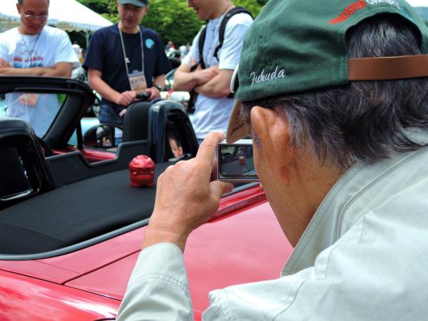 中山さんの愛車の上でNDろどすたくんを撮影する福田さん